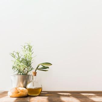 Pote de romero con botella de aceite de oliva fresca y bollo en la mesa de madera
