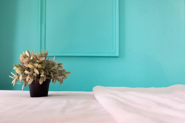 Pote de la planta en la cama blanca en dormitorio en casa.