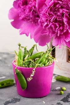 Pote púrpura con guisantes verdes y peonías.