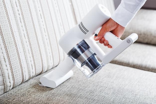 Potente aspiradora inalámbrica con tecnología de recolección de polvo ciclónico blanco en la mano, limpia la alfombra de la casa cerca del sofá. de cerca