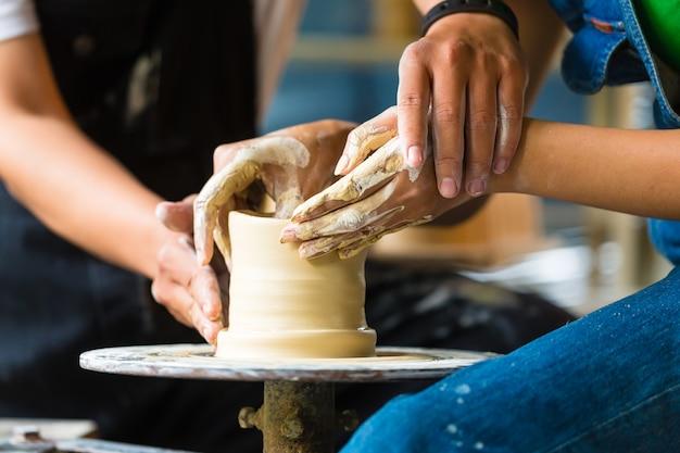 Potter creando un tazón de arcilla en la rueda giratoria.