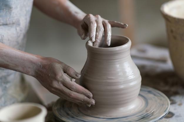 Potter esculpe un jarrón en el torno de alfarero