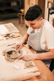 Potter femenino sonriente que da forma a la arcilla del molde en el escritorio de madera