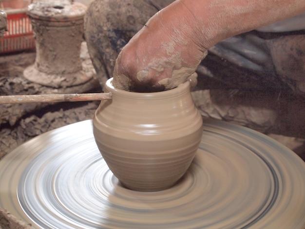 Potter hace en la olla de barro la rueda de alfarería.