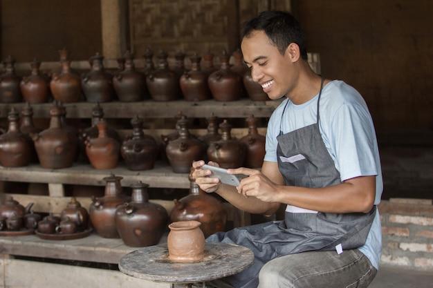 Potter hombre tomando foto de su producto en el taller de cerámica