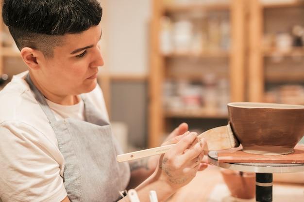 Potter mujer pintando el tazón de fuente hecho a mano con pincel en el taller