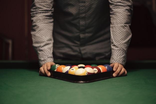 Poule de billar americano. triángulo de bolas de billar. un hombre preparándose para comenzar un juego de billar.