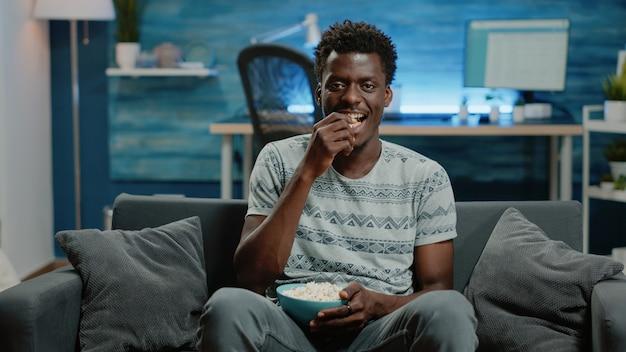Pov de adultos viendo comedia en televisión con palomitas de maíz