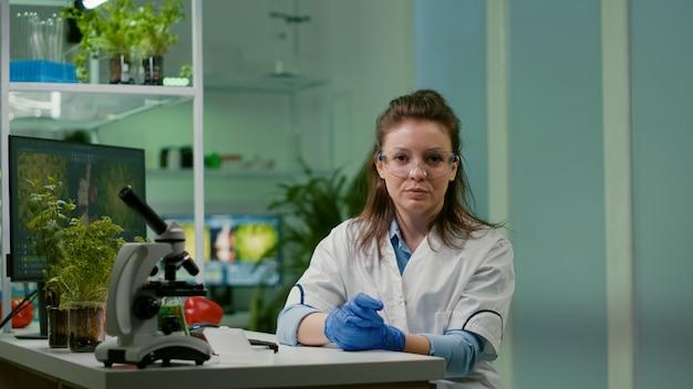 Pov de mujer botánica con bata blanca escuchando al equipo de químicos durante una videollamada en línea