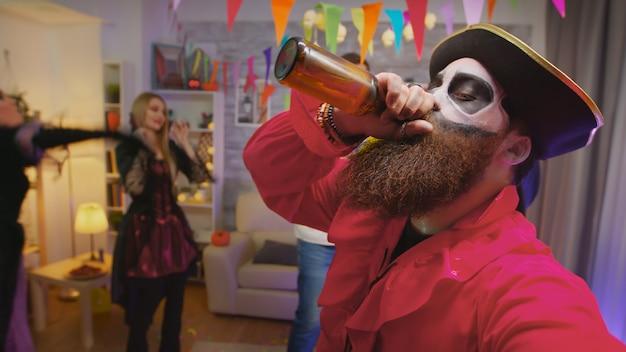 Pov de pirata barbudo celebrando halloween con sus amigos invitando a todos a la fiesta mientras otros personajes de miedo bailan en el fondo en la casa decorada