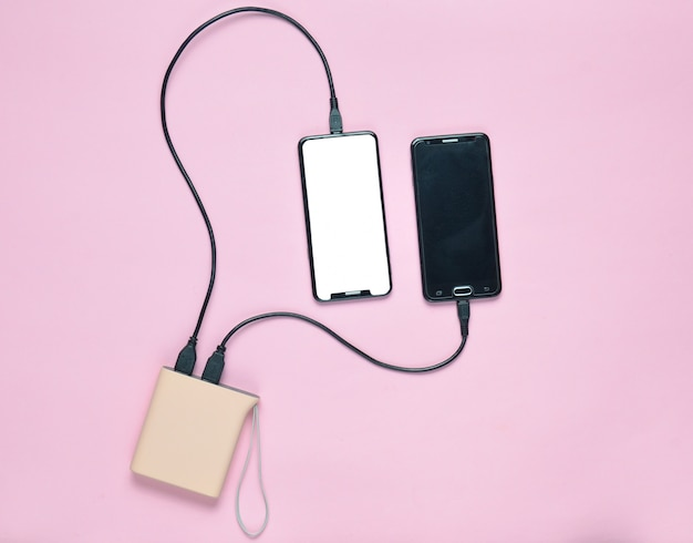 Power bank carga dos teléfonos inteligentes en una superficie en colores pastel. aparatos modernos. vista superior. minimalismo