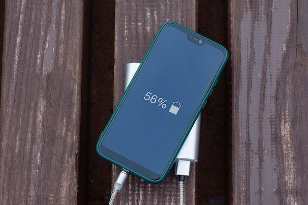 Power bank carga un teléfono inteligente en un banco de madera en el parque.