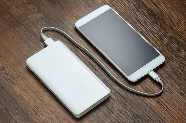 Powerbank y teléfono móvil en la mesa de madera
