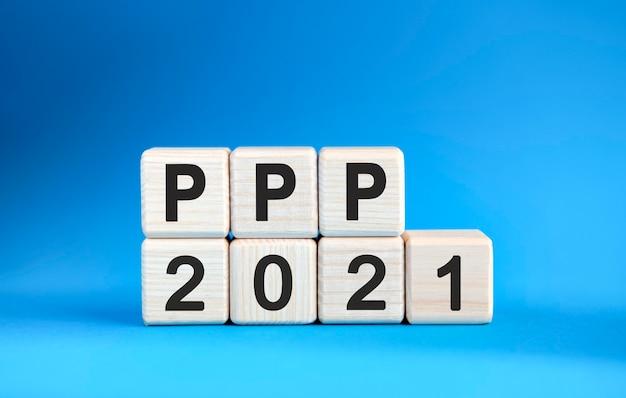 Ppp 2021 años en cubos de madera sobre un fondo azul.