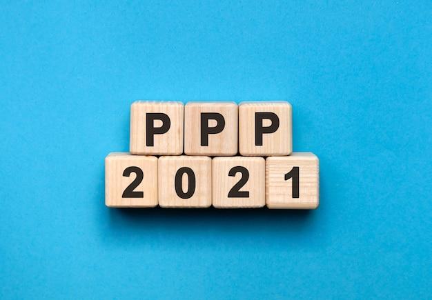 Ppp - concepto de texto en cubos de madera con fondo azul degradado.