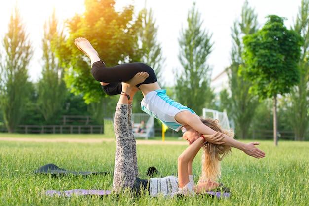 Practica acroyoga en la naturaleza con dos chicas