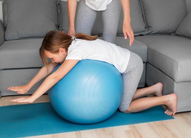 Práctica deportiva de la madre y la niña en la pelota que rebota