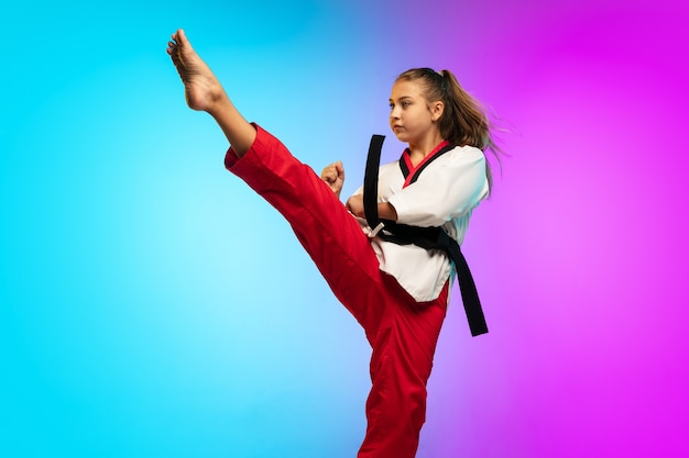 Práctica. karate, taekwondo chica con cinturón negro aislado en gradiente