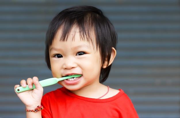 Práctica de niña asiática a cepillarse los dientes.