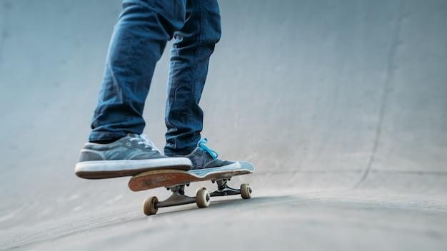 Práctica de patinador urbano. hombre montando patineta. tiro de piernas en jeans. rampa del parque de patinaje.