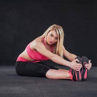 Practica de yoga. chica en el gimnasio realiza estiramientos.