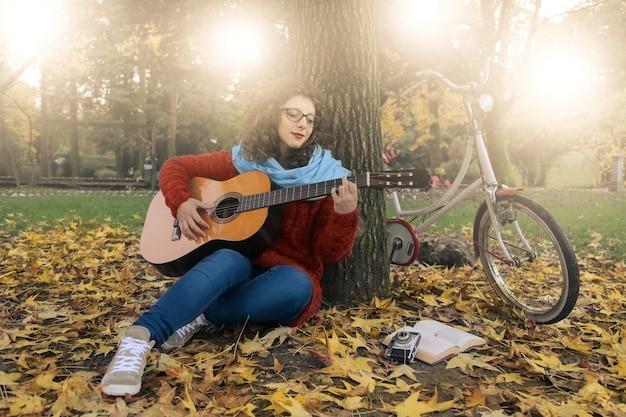 Practicando una guitarra en un parque