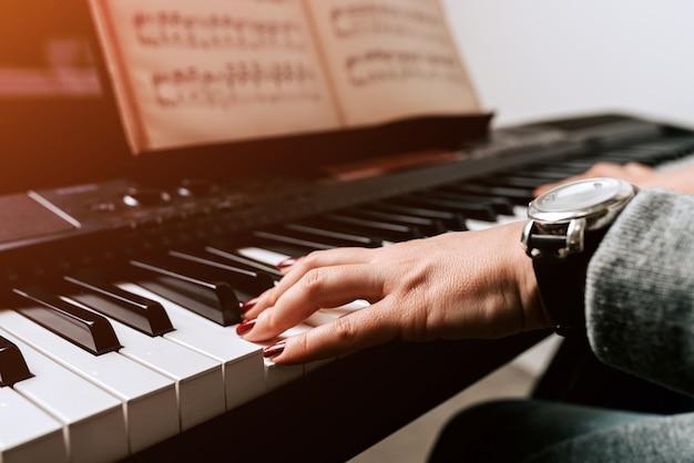 Practicando el piano tocando partituras en el sintetizador.