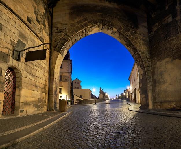 Praga romántica al amanecer, entrada al puente de carlos a través del arco iluminado del puente de la ciudad pequeña