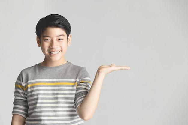 Preadolescente asiático presentando algo en mano sobre fondo gris.