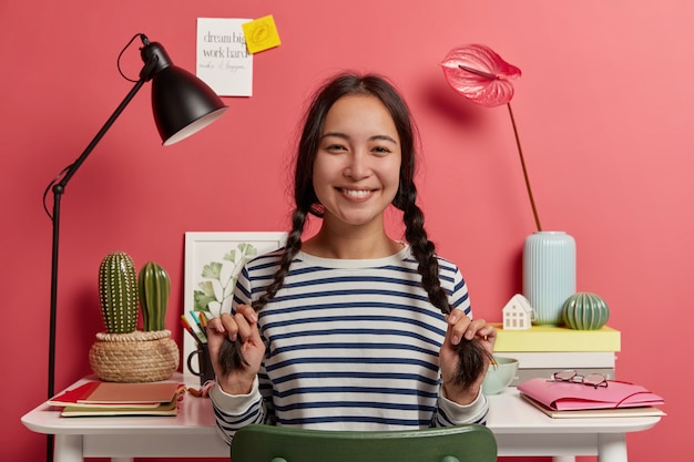 Preciosa colegiala se divierte mientras se prepara para los exámenes, tiene dos largas trenzas, sonríe feliz, vestida con un suéter a rayas, planea el horario para el próximo mes
