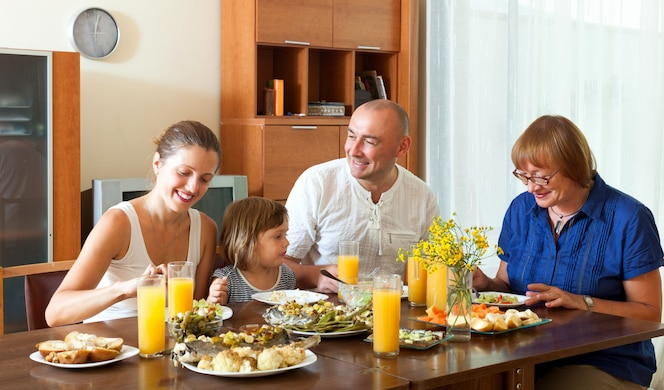 Preciosa familia feliz multigeneración tener una cena saludable