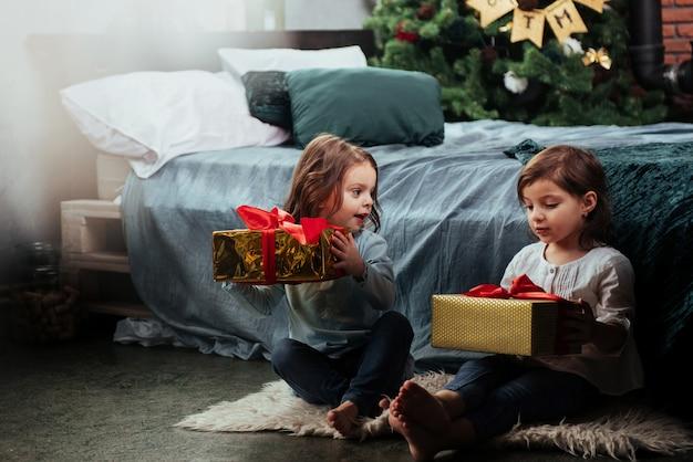 Preciosa habitación decorada. vacaciones de navidad con regalos para estos dos niños que se sientan en el interior en la bonita habitación cerca de la cama