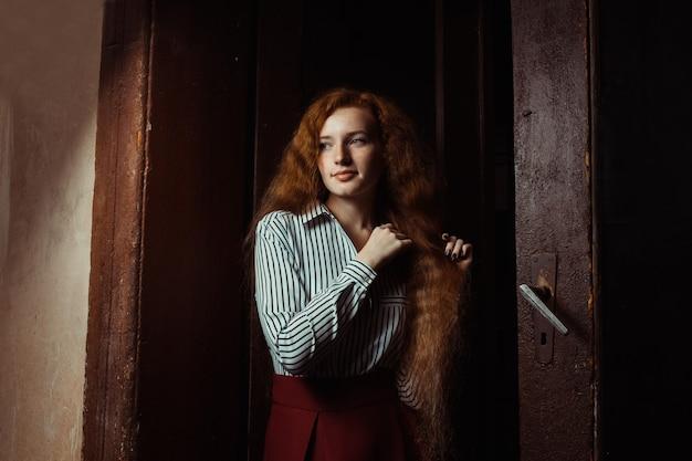 Preciosa joven modelo pelirroja con cabello largo y exuberante. mujer, posar, en, un, cuarto oscuro