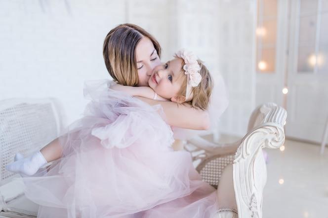 Preciosa madre e hija se abrazan tiernamente sentado en una silla blanca