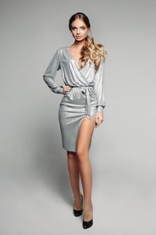 Preciosa modelo en brillante vestido de cóctel plateado y tacones.