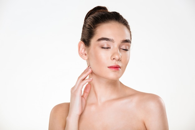 Preciosa modelo femenina con cabello castaño en moño que disfruta con los ojos cerrados mientras hace un tratamiento para el cuidado de la piel