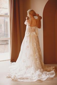 Preciosa modelo con maquillaje nupcial y peinado en vestido de encaje de matrimonio.