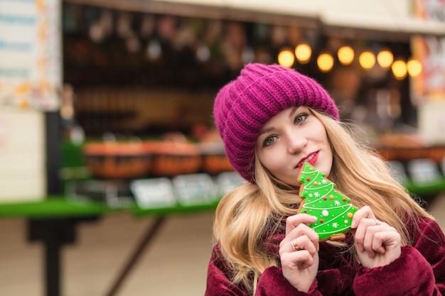 Preciosa modelo rubia sosteniendo una deliciosa galleta de jengibre navideña en la calle en kiev