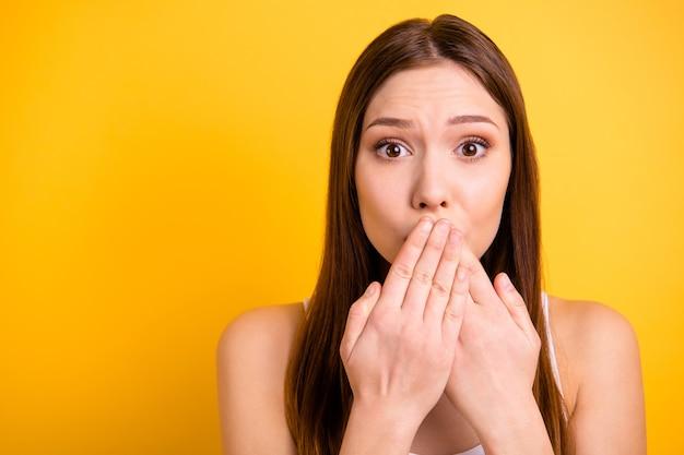 Preciosa mujer morena con labios rojos posando contra la pared amarilla