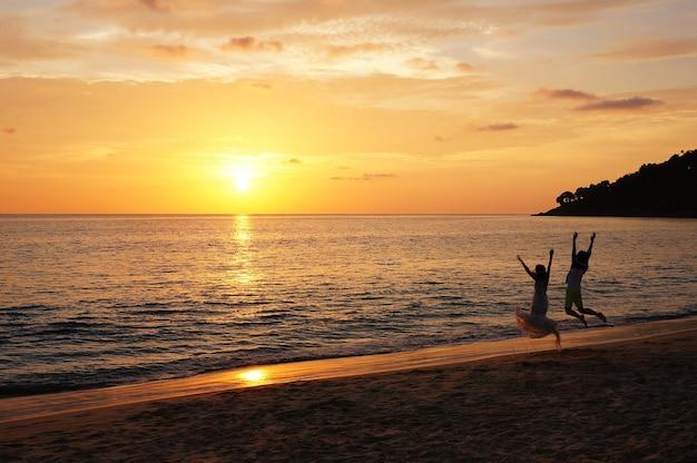 Preciosa puesta de sol con una pareja saltando.