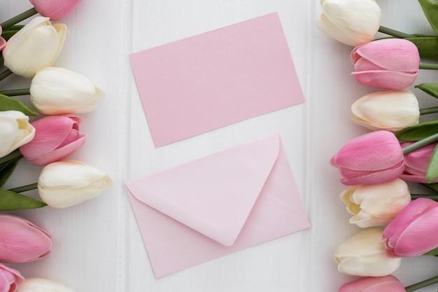 Preciosa tarjeta de felicitación y sobre con flores de tulipanes sobre fondo blanco de madera