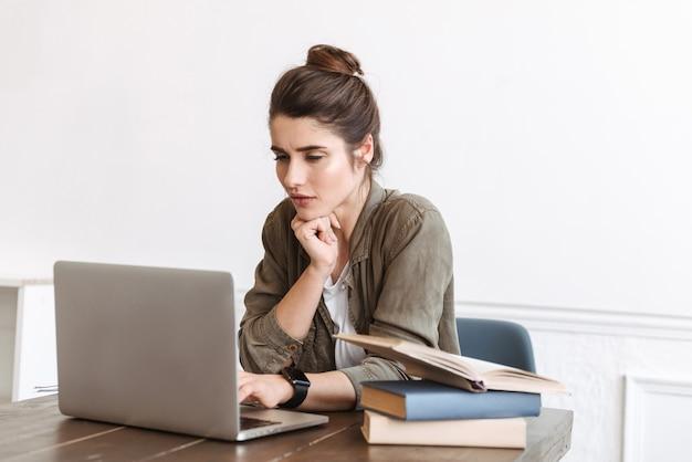 Precioso joven estudiante pensativo que estudia con ordenador portátil en el interior