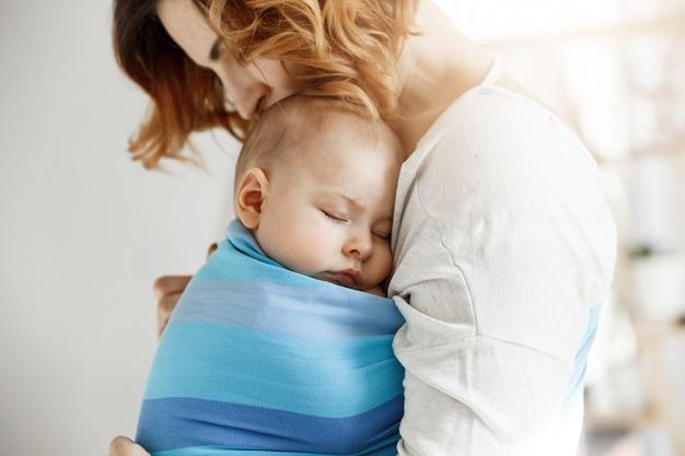 Precioso niño recién nacido que duerme profundamente en el día en el pecho de la madre en azul honda del bebé. mamá besa la cabeza del bebé y se siente relajada y encantada. concepto de familia