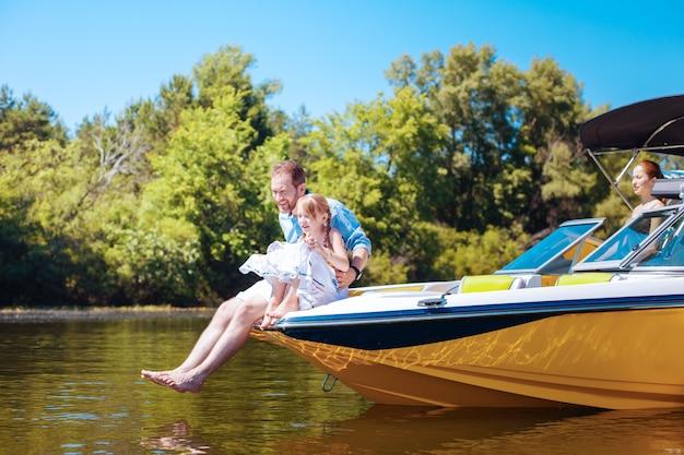 Precioso tiempo juntos. padre joven optimista y su pequeña hija sentados en la proa del barco y observando peces en el agua del río