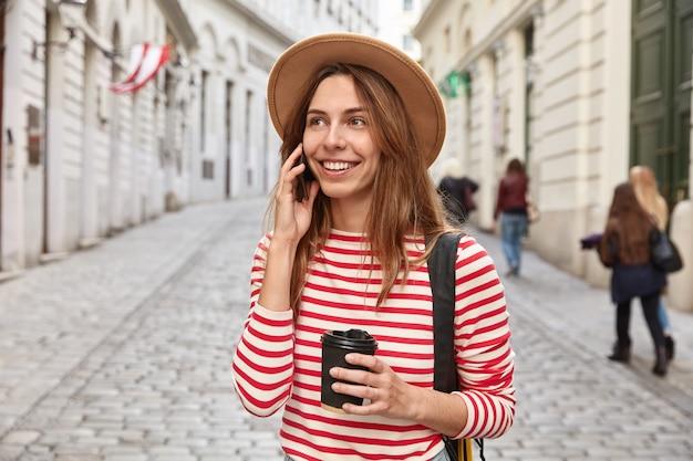 Precioso turista sonriente pasea por la ciudad, tiene una conversación telefónica, tiene café para llevar, se concentra en algún lugar en la distancia