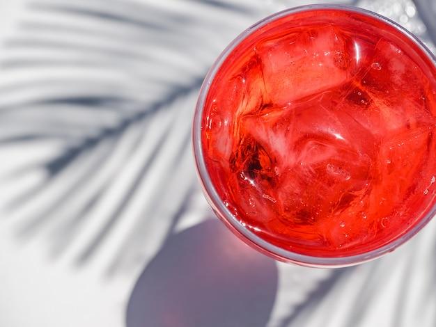 Precioso vaso con cóctel rosa y hielo.