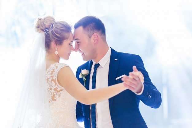Preciosos recién casados bailan un baile de bodas.