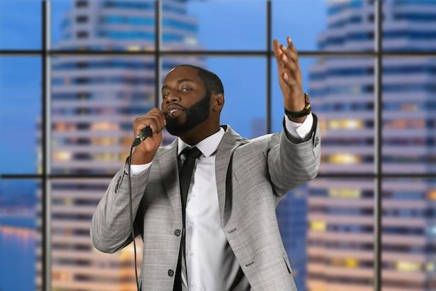 Predicador negro hablando por micrófono.