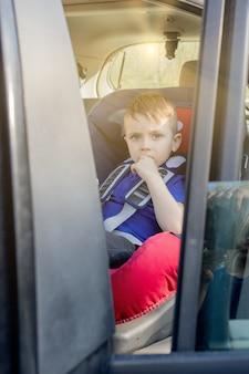 Preescolar lindo niño de 3-4 años sentado en el asiento de seguridad y llorando durante el viaje familiar en automóvil
