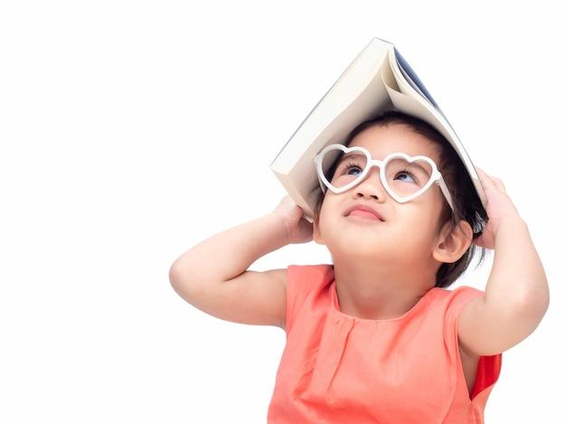 Preescolar niño encantador con el libro que cubre su cabeza y mirando el libro.